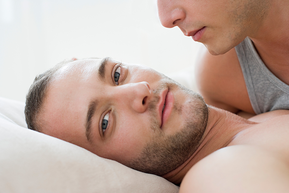 Close up of a man's face lying on a pillow. His lover's mouth hovers close above him.