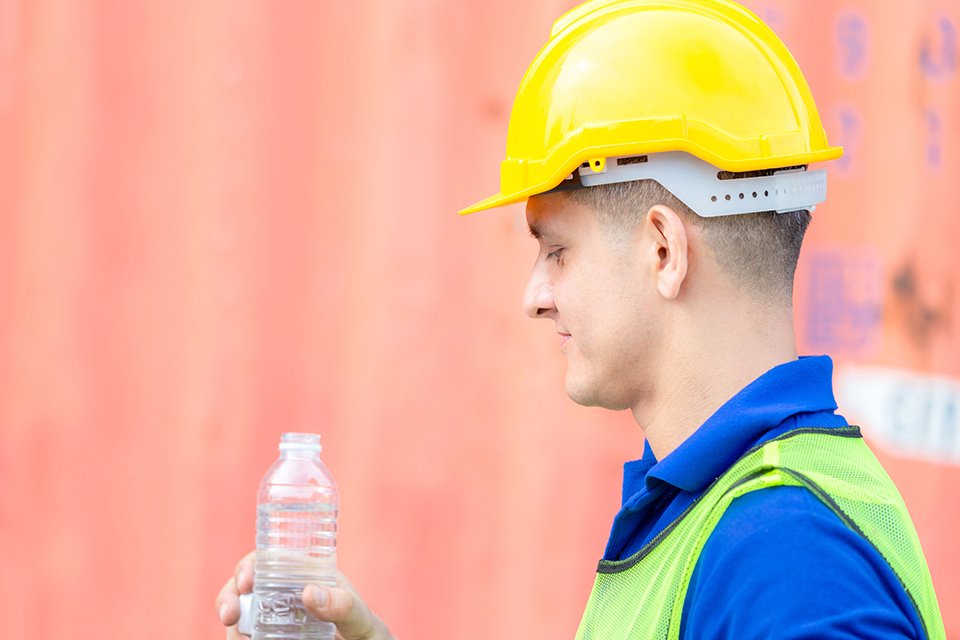 Close up of construction worker in hard hat drinking water